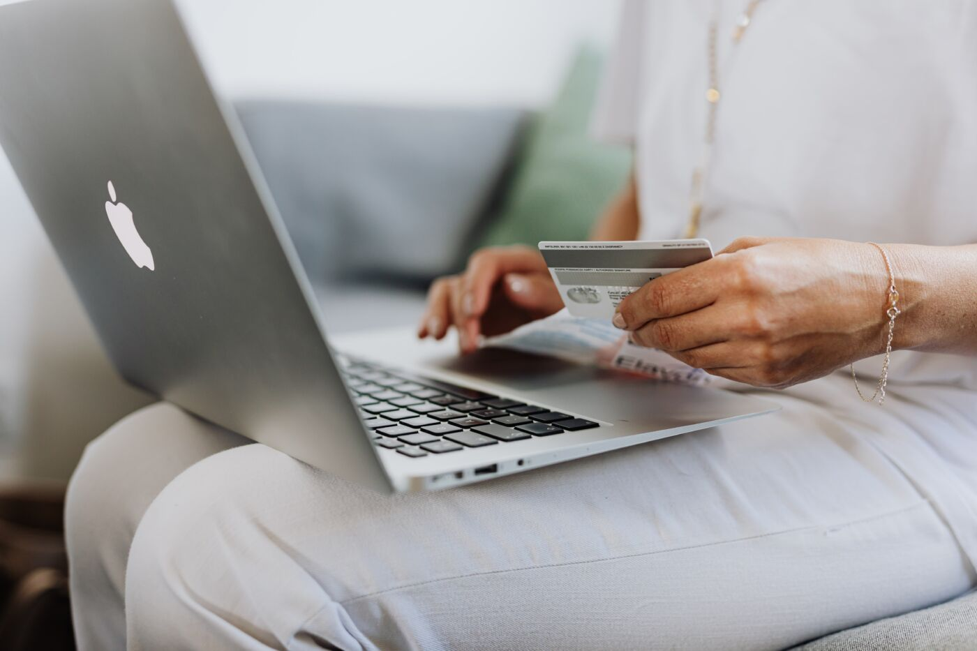 how to save money shopping online - person holding credit card shopping on computer